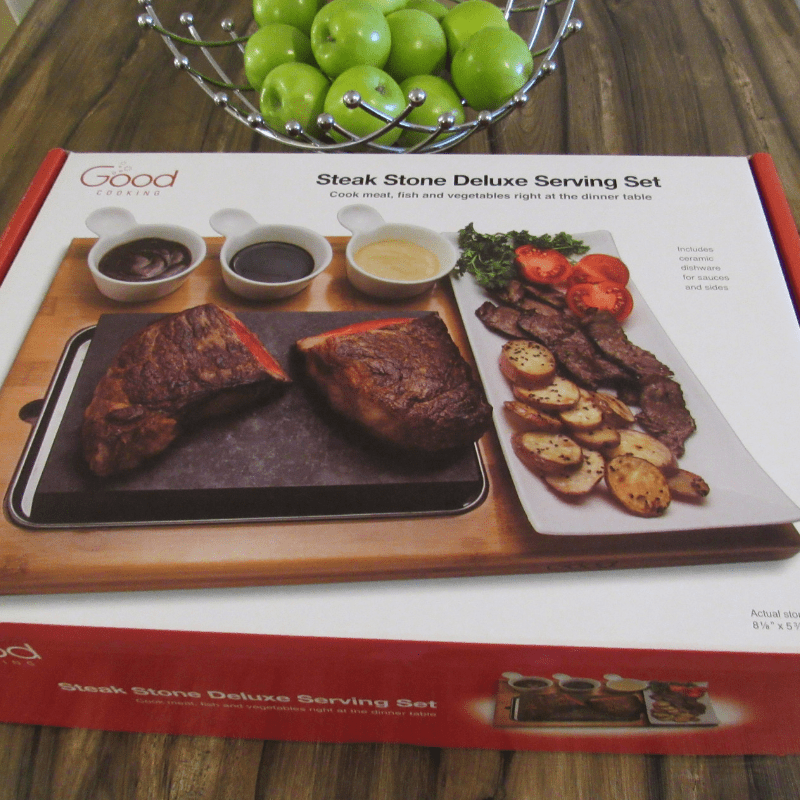 The Good Cooking Steak Stone Serving Set is the perfect way to cook meat, fish, vegetables and more for your guests right at the dinner table! Just heat your steak stone in the oven, remove and place on the stainless-steel tray and bamboo platter! Made from hand-crafted basalt stone, the steak stone is easy to clean and a safe way to enjoy your favorite meals. Available as a family size serving set with an extra-large basalt stone, or deluxe serving set with a ceramic side dish and 3 ceramic sauce cups.